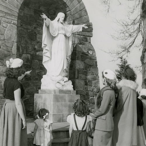 Three women and four children stand in front of the Sacred Heart Shrine by Lake Michigan, as one woman points toward the statue