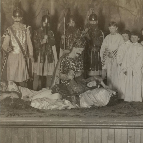 A student actor dressed as royalty holds the hand of another actor lying prone on the ground, as other actors stand around them