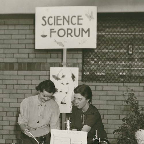 Six students stand at tables with exhibits about various kinds of science, with a sign above them reading Science Forum