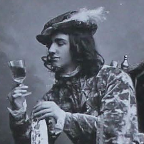 James Griffin, in costume as Prince Hal, sits in a high-backed chair with his feet apart and right elbow on the table, gazing at the drink in his right hand