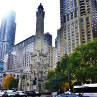 Loyola's Downtown campus with skyscapers around it and cars driving by.